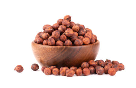 Pile of brown chickpeas in wooden bowl, isolated on white background. Brown chickpea. Garbanzo, bengal gram or chick pea bean.