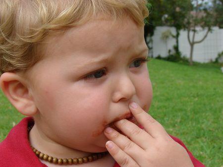 Niño fuera de comer chocolate Foto de archivo - 697969