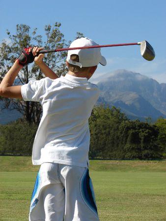 Chico joven tras su pelota después de un tiro en el campo de golf con un conductor  Foto de archivo - 847161