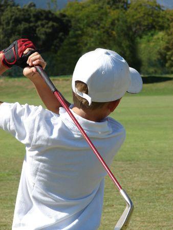 Niño después de su bola después de un tiro en el campo de golf con un hierro Foto de archivo - 847158