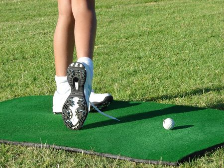 Young golfer legs on a range mat during a lesson
