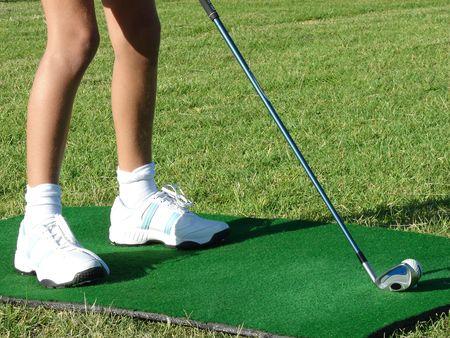 Jóvenes golfista piernas sobre una amplia gama MAT durante una lección Foto de archivo - 847156