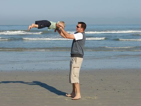 Father and son playing swing swing on the beach Stock Photo - 951903