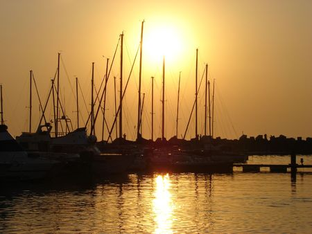 Boats in the harbour as the sun is setting photo