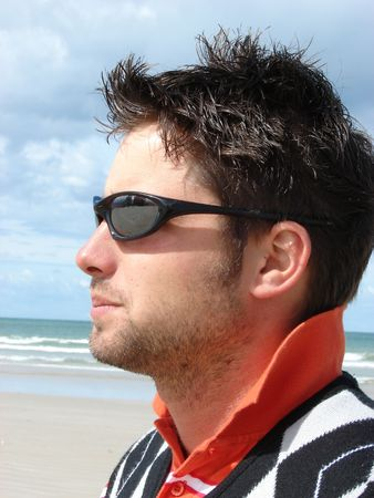 Profile of a young man wearing sunglasses, on the beach