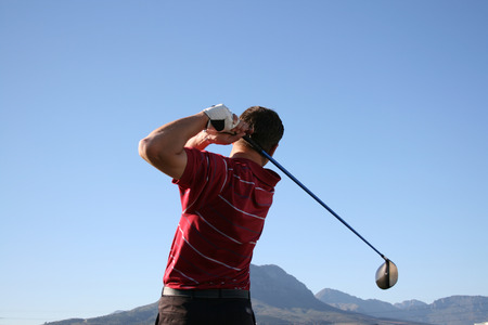 Golfer shot with a driver against blue sky Follow Through of a young professional golfer whilst practising on the range