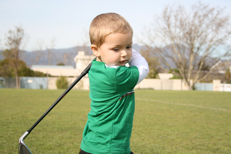 Young golfer concentrating during a practise session on the range