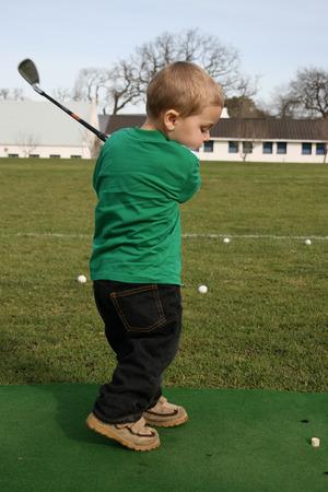Chico joven la práctica de su campo de golf en el driving range  Foto de archivo - 1404859