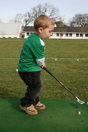 driving range: Young boy practising golf on the driving range
