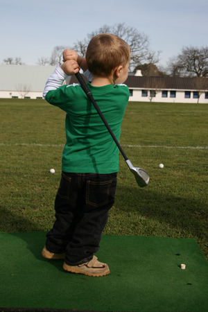 driving range: Young boy practising on the driving range Stock Photo
