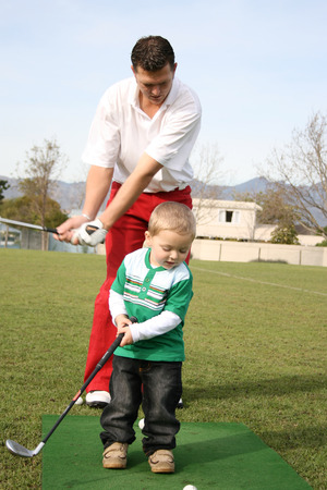 driving range: Toddler and his father practising on the golf driving range Stock Photo