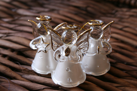 Three white glass angels on a rustic background photo