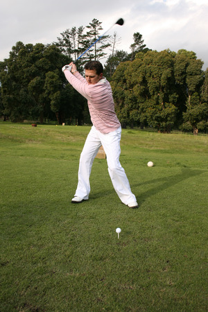 Young golfer during a shot with his driver photo