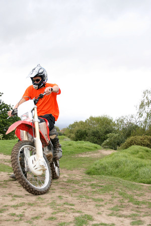 Young biker coming up the hill on a dirt track Stock Photo - 1717417