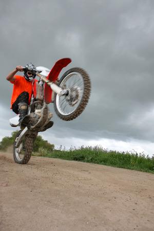 Young biker on an off-road bike doing tricks photo