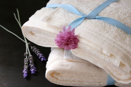 heaped: Heaped towels with blue ribbon and fresh flowers Stock Photo