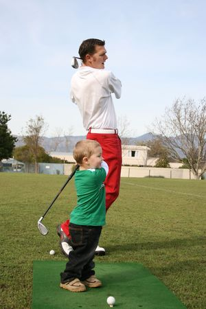 Young boy and his father practising on the driving range Stock Photo