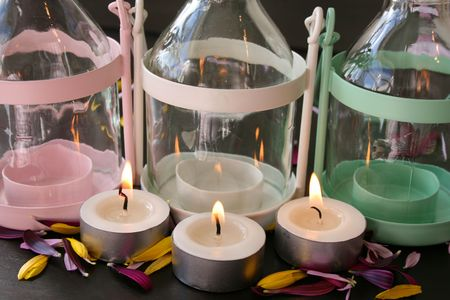 candleholders: Three candleholders with lit candles infront of them