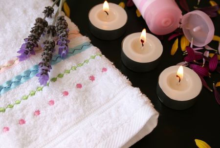 Hand Towel with candles and handcream and fresh flowers Фото со стока