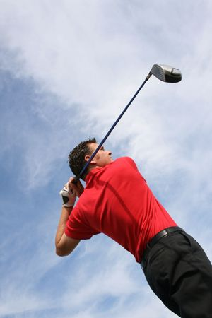 Young golfer at an angle hitting a driver