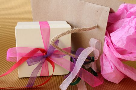 Cream colored gift box and brown gift bag with ribbons photo