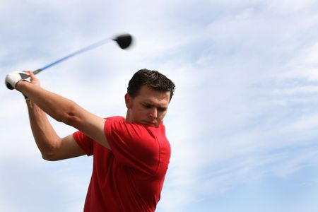 Young golfer hitting a driver against a half cloudy sky