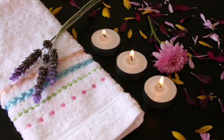 face cloth: Soft pink flower with spread petals, a face cloth and candles Stock Photo