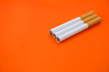 habbit: Three cigarettes on an orange background with copy space