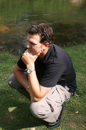 young male model: Los chicos modelo sentados en el c�sped junto a un arroyo someras