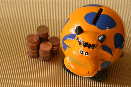 coppers: Stacks of money next to a money box Stock Photo