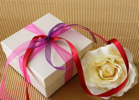 Cream colored gift box and a cream colored rose Фото со стока