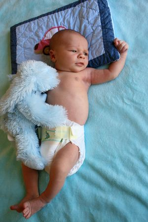 peacefull: Week old baby boy on a blue blanket early in the morning Stock Photo