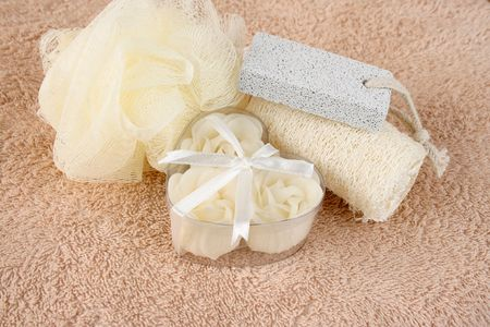 White flower soaps with bath set on towel photo
