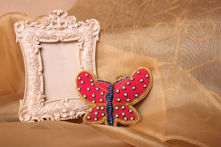 old photo: Empty Picture frame and a red beaded butterfly