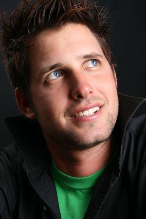 black hair blue eyes: Male model in studio against black background