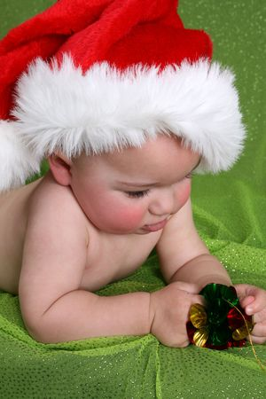 Baby lying on his tummy, wearing a christmas hat
