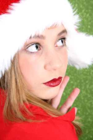 Teenager with red lips wearing a christmas hat photo
