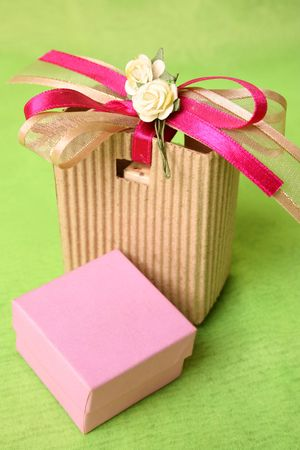 Pink gift box and brown gift bag with ribbons photo