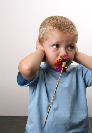 Toddler playing with a wind toy, holding his ears Stock Photo - 3642442