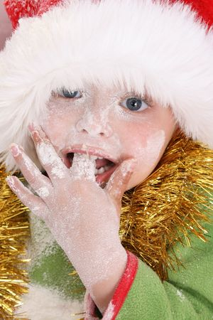 Toddler wearing a christmas hat, baking christmas cookies Stock Photo - 3679012