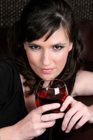 Female model with intense eyes holding a glass of red wine Stock Photo