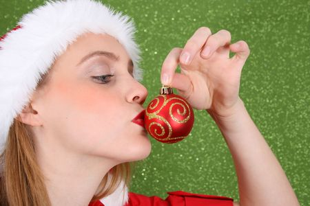 Christmas girl kissing a red and gold decoration Stock Photo