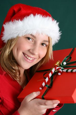 Teenager wearing a christmas hat, holding a present Stock Photo