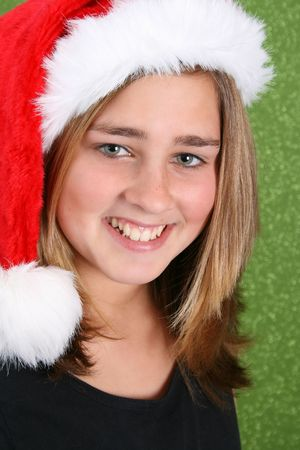 Smiling Teen wearing a christmas hat against a green background Stock Photo - 3825510