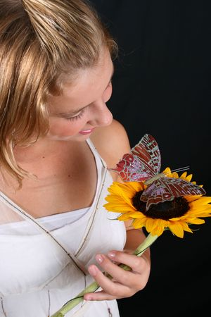 Teenage female model holding a sunflower with a butterfly photo