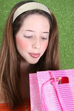 Brunette teenager peeping into a pink gift bag photo