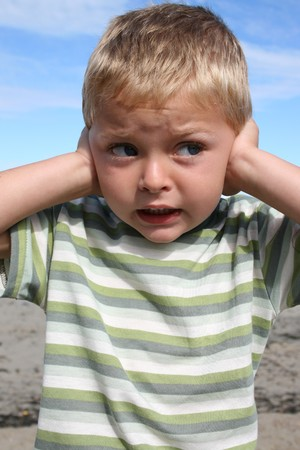 Young blond boy at the beach, closing his ears Stock Photo - 4175580