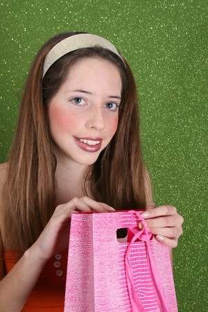 Brunette teenager on a green background opening a gift photo