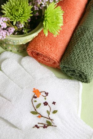 Spa Accessories setting with face cloths, scrub gloves and flowers Banque d'images