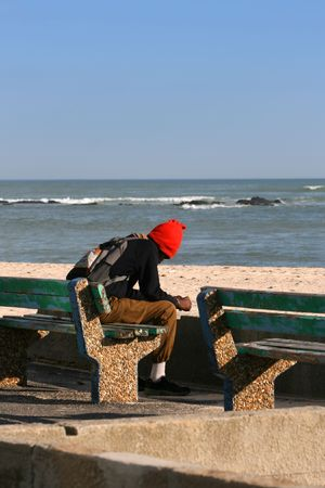 Lonely man sitting on a bench near the sea photo